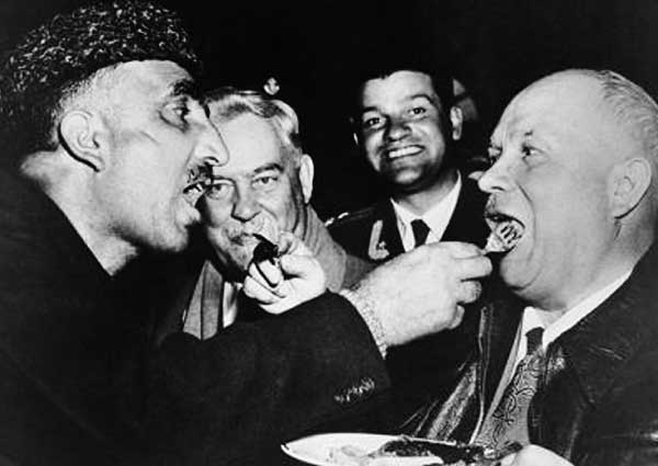 Khruschev feeds a friend and his friend feeds him. Those nearby are delightfully amused.