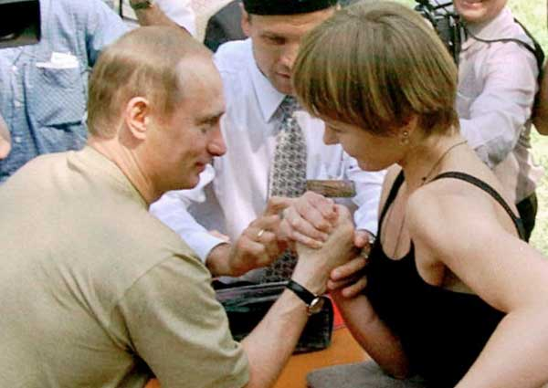 Putin with shirt on, showing a woman in Kazan who's the boss.